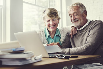 Couple smiling looking at a laptop